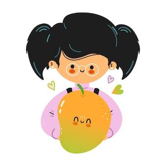 Młoda śliczna zabawna mała dziewczynka trzyma mango w ręku