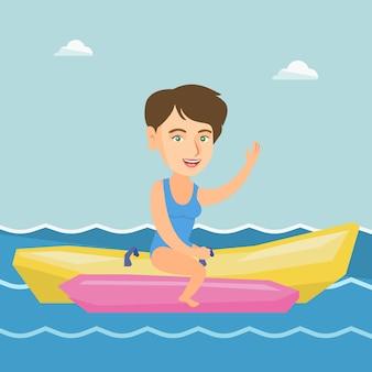 Młoda szczęśliwa caucasian kobieta jedzie bananową łódź.