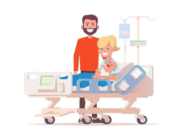 Młoda szczęśliwa para z ich noworodkiem na łóżku szpitalnym.