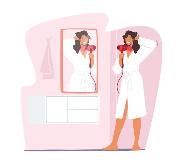 Młoda urocza kobieta stoi przed lustrem, suszy mokre włosy suszarką do włosów