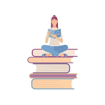 Młoda uśmiechnięta kobieta czytanie książki siedząc na stosie gigantycznych książek