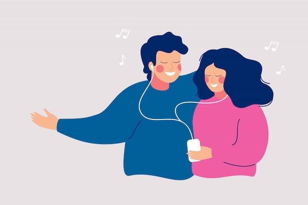 Młoda wesoła para dzieli się słuchawkami i słucha muzyki za pomocą telefonu komórkowego.