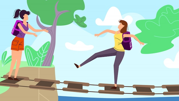 Młode kobiety chodzi wzdłuż zataczającego się mostu wiszącego w lesie lub parku.