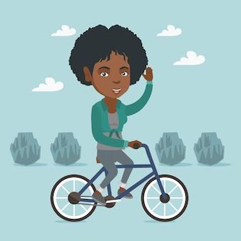 Młodej afrykańskiej kobiety jeździecki bicykl w parku.