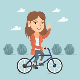 Młodej caucasian kobiety jeździecki bicykl w parku.