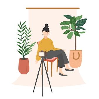 Młodej kobiety blogger siedzi na krześle i bierze selfie w domu. dziewczyna tworzy nowe treści wideo na blogu, tworząc nowy post w mediach społecznościowych. ilustracja nowoczesny styl płaski kreskówka