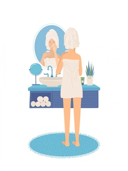 Młodej kobiety pozycja w łazience i patrzeć jej odbicie w lustrze