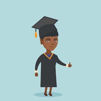 Młody afroamerykański absolwent daje kciukowi up.