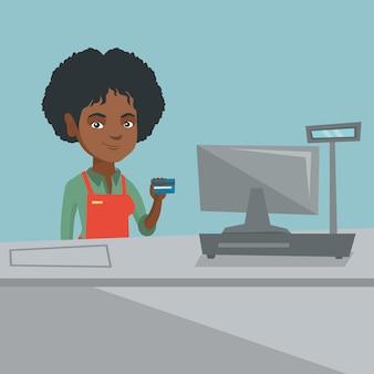 Młody afroamerykański kasjer trzyma kartę kredytową