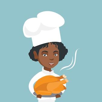 Młody afrykański szef kuchni trzyma pieczonego kurczaka.