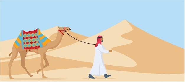 Młody arabski facet chodzi jego wielbłądzia synkliny pustynia