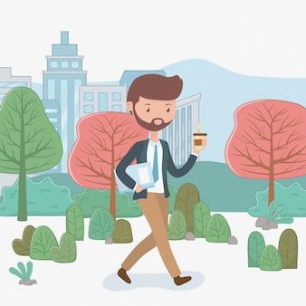 Młody biznesmen z kawowym odprowadzeniem w parku