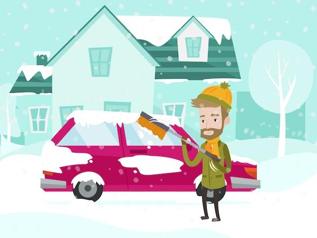 Młody caucasian białego człowieka cleaning samochód od śniegu.