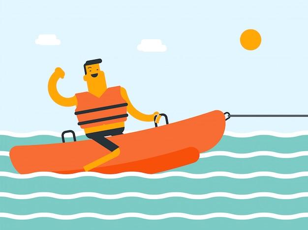 Młody caucasian biały człowiek jedzie bananową łódź.