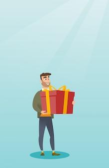 Młody caucasian mężczyzna mienia pudełko z prezentem.