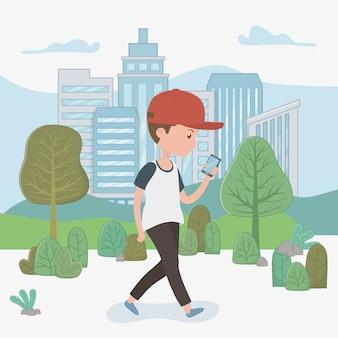 Młody chłopak spaceru za pomocą smartfona w parku