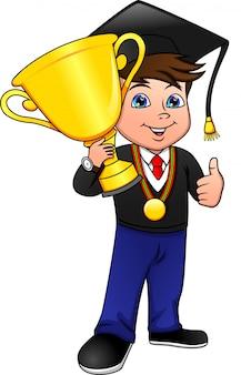 Młody chłopiec kończy szkołę i trzyma zwycięski złoty puchar