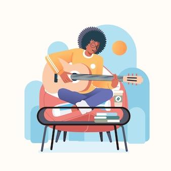 Młody czarny afro mężczyzna grający na gitarze i śpiewający, siedzący na kanapie i biurku z kawą