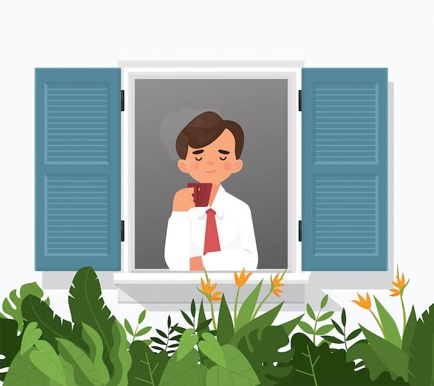 Młody człowiek cieszyć się kawą lub herbatą w oknie