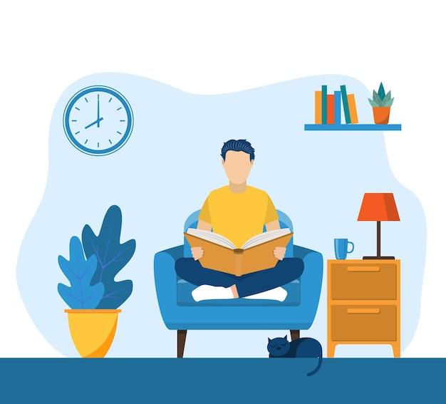 Młody człowiek czyta książkę na krześle w domu