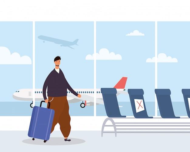 Młody człowiek dorywczo z walizką na lotnisku