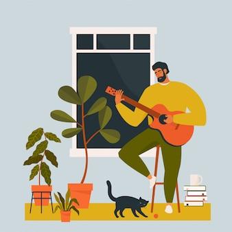 Młody człowiek gra na gitarze w domu przez okno