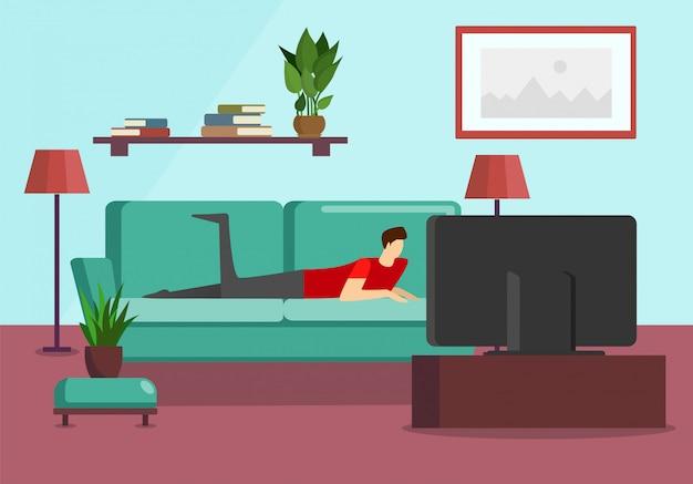 Młody człowiek oglądać program telewizyjny leżąc na kanapie