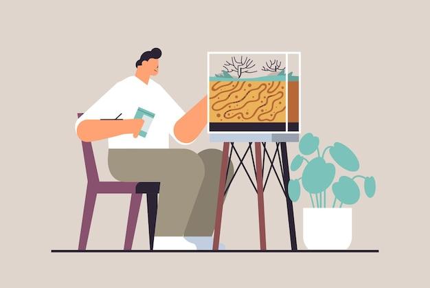 Młody człowiek opiekujący się facetem z farmy mrówek karmiącym mrówki w formikarium koncepcja owadów domowych pełnej długości poziomej ilustracji wektorowych