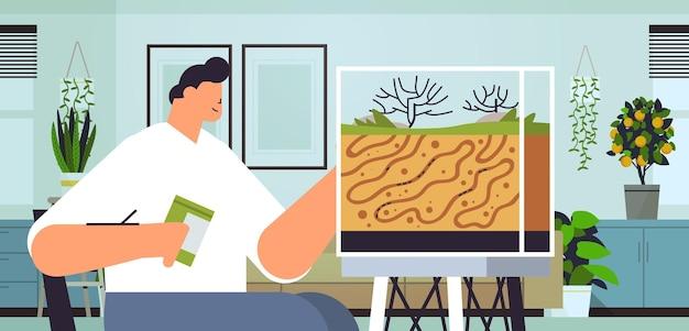 Młody człowiek opiekujący się facetem z farmy mrówek karmiącym mrówki w formikarium koncepcja owadów domowych wnętrza salonu