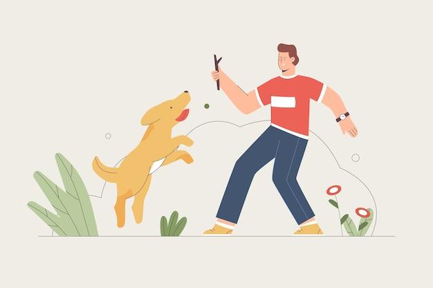 Młody człowiek trenuje psa z kijem