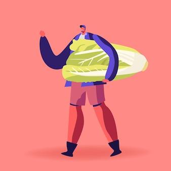 Młody człowiek trzyma ogromną kapustę chińską