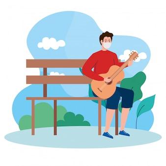 Młody człowiek ubrany w maskę medyczną, gra na gitarze, siedząc na krześle w parku