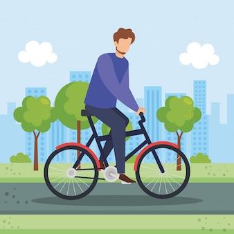 Młody człowiek w bicyklu w parku