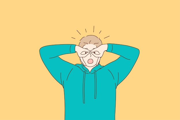 Młody człowiek w zielonej bluzie z kapturem czuje się szalony, zakrywając oczy palcami jak okulary na żółtym tle
