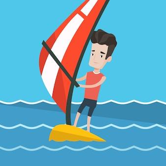 Młody człowiek windsurfing na morzu.