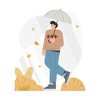 Młody człowiek z parasolem przechodzi przez jesień.