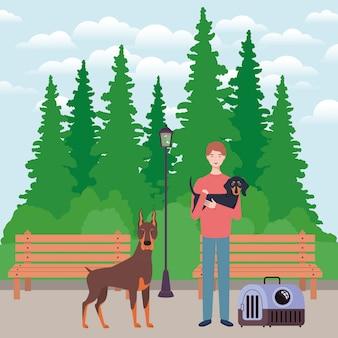 Młody człowiek z ślicznymi psami maskotkami w parku