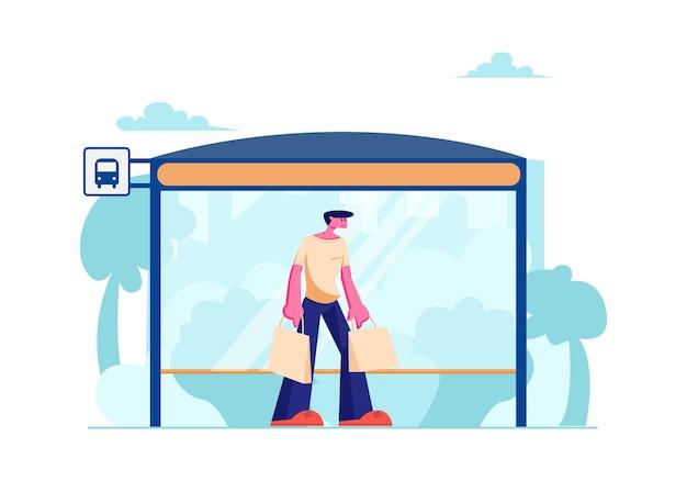 Młody człowiek z torby na zakupy stoi na dworcu autobusowym z ławką czeka na publiczny transport miejski