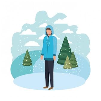 Młody człowiek z zimowymi ubraniami i zimową sosną