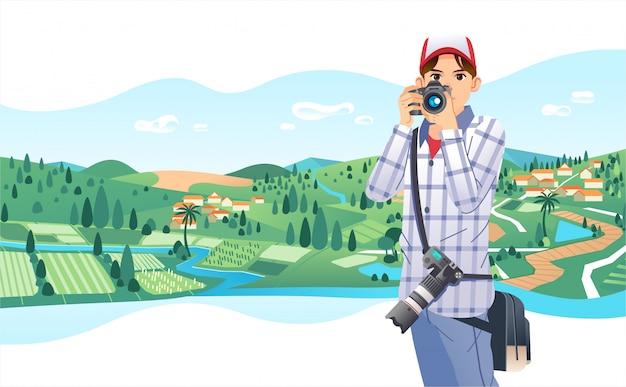 Młody fotograf w kapeluszu i przynieść torbę na talię robi zdjęcie wiejskiego krajobrazu