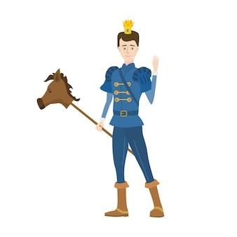 Młody książę z koroną w średniowiecznym bajkowym kostiumie i zabawkowym konikiem na patyku.