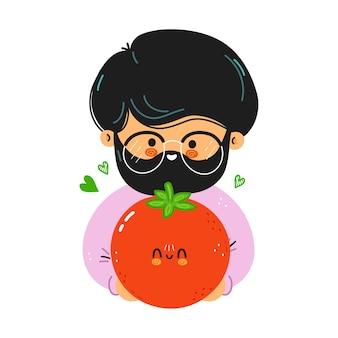Młody ładny zabawny człowiek trzyma pomidora w ręku