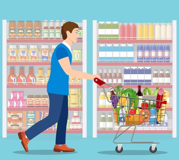 Młody mężczyzna pchający wózek na zakupy w supermarkecie pełen artykułów spożywczych