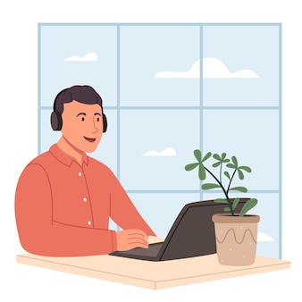 Młody mężczyzna siedzący przy laptopie w słuchawkach