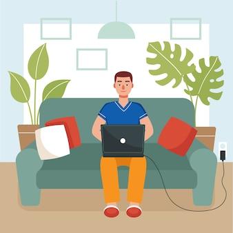 Młody mężczyzna siedzi na kanapie i pracuje na laptopie