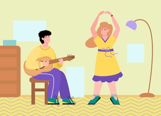 Młody mężczyzna siedzi na krześle, gra na gitarze i kobieta tańczy obok niego