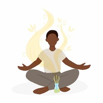 Młody mężczyzna siedzi w pozycji lotosu z dyfuzorem zapachu.