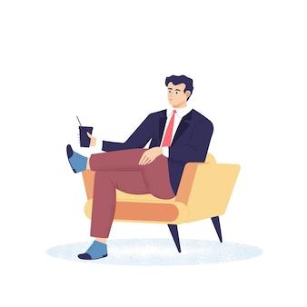 Młody mężczyzna siedzi w wygodnym fotelu
