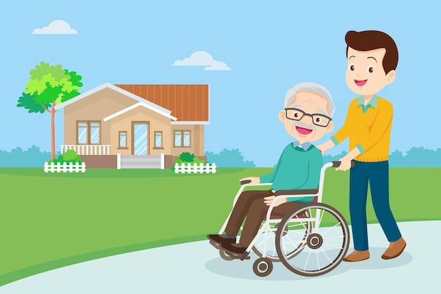 Młody mężczyzna spacerujący ze starszym mężczyzną na wózku inwalidzkim