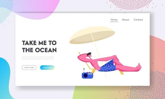 Młody mężczyzna wyleguje się na szezlongu pod parasolem na plaży morskiej